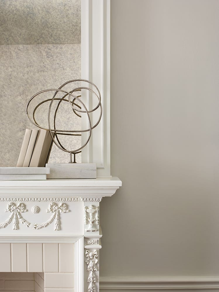 close-up of white ornate fireplace mantle against cream wall