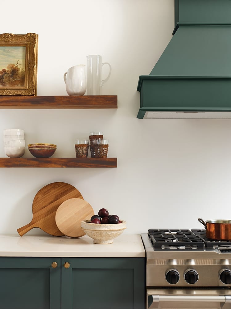 kitchen with cream walls, wooden floating shelves and dark green accent colors