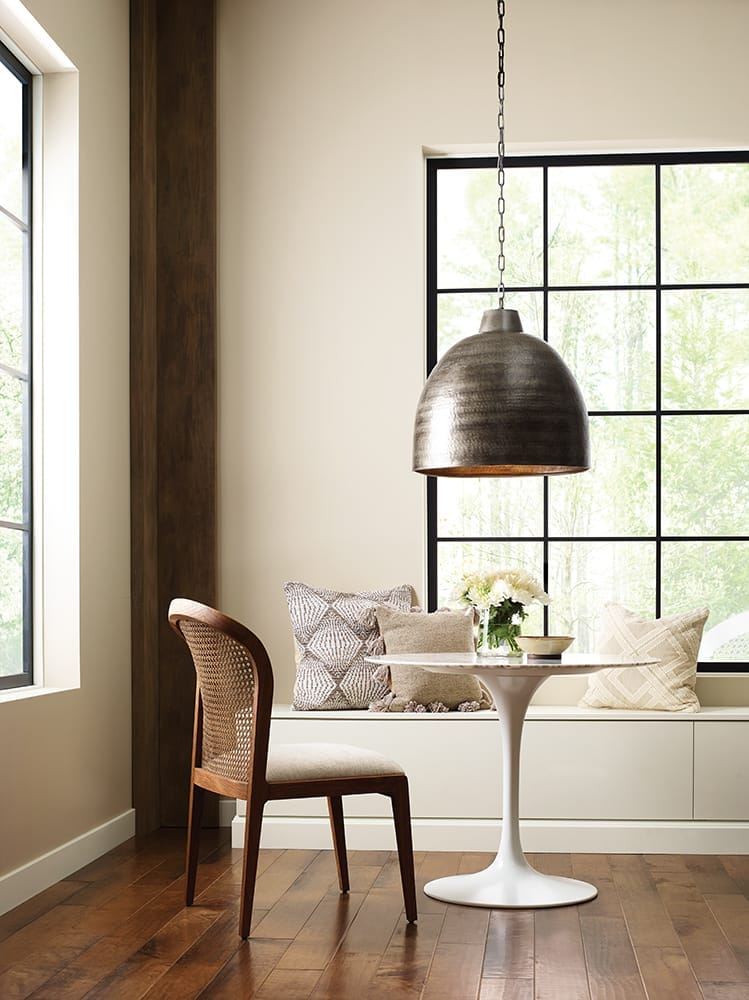 beige dining room with wicker, marble and metal finishes and patterned pillows