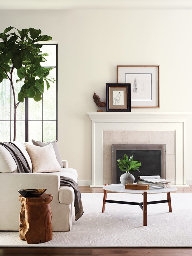 inviting casual living in soft cream and beige with fireplace, artwork and plants