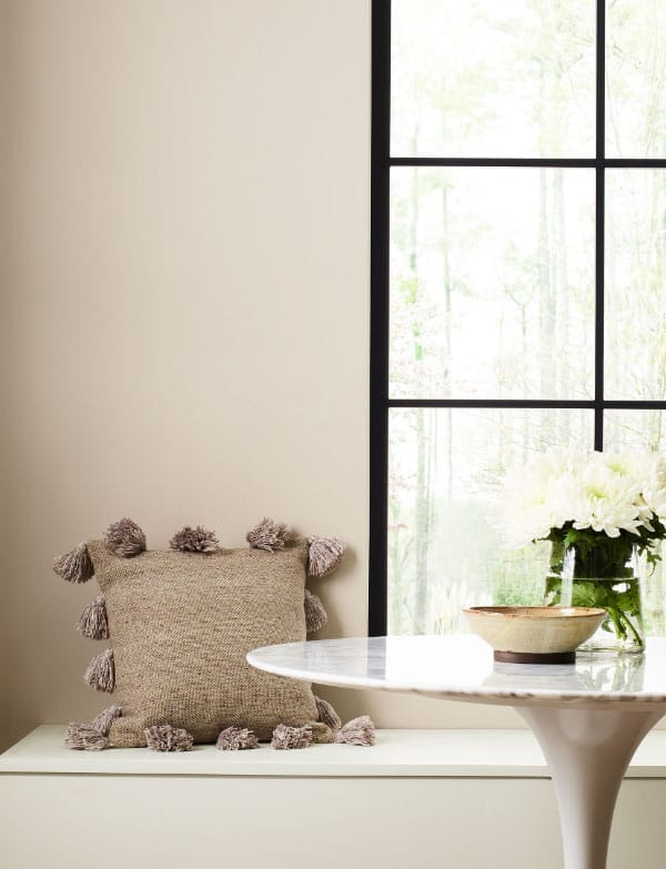 dining nook with large window, marble table and textured pillow