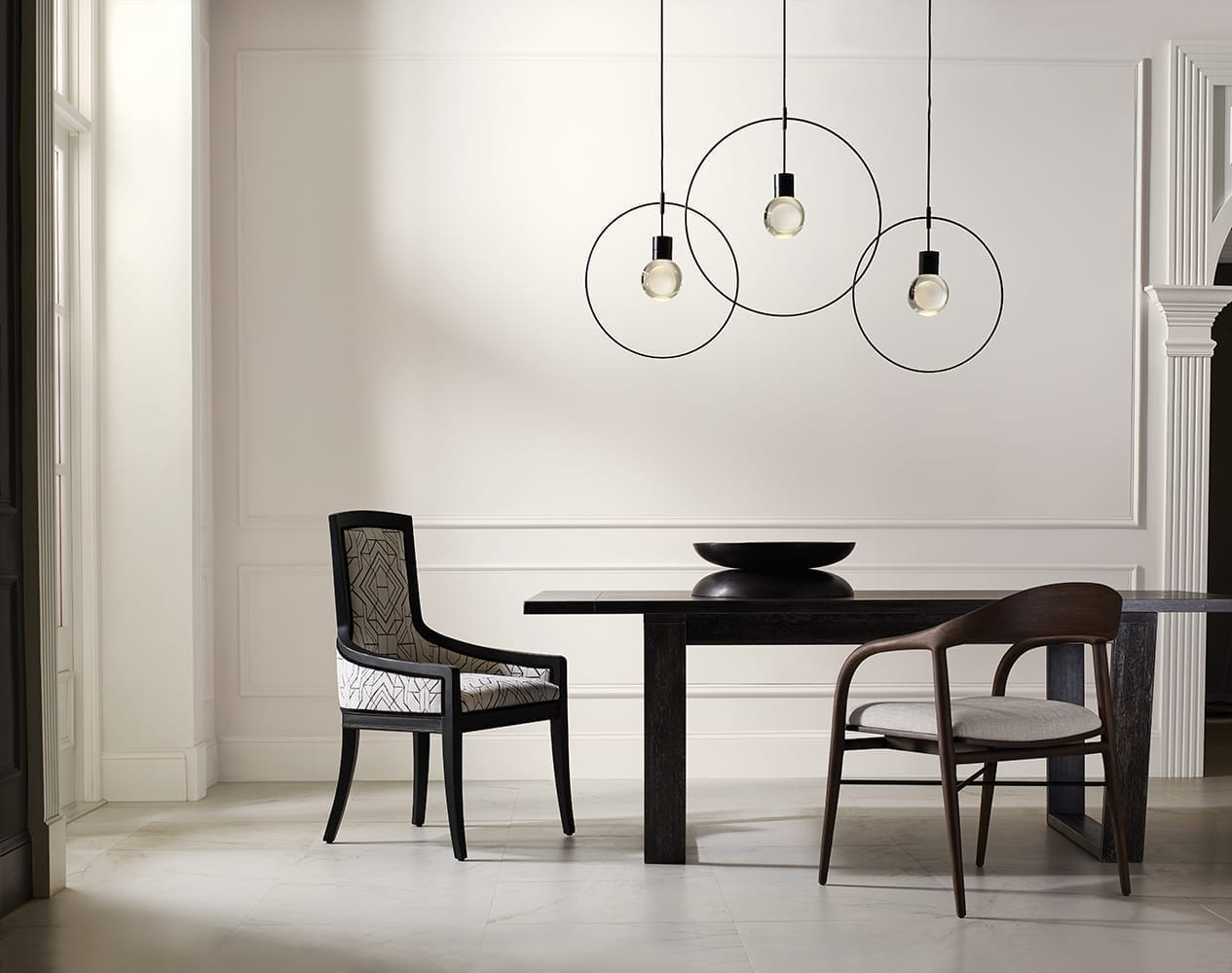 cream dining room with ebony table and modern, mismatched chairs