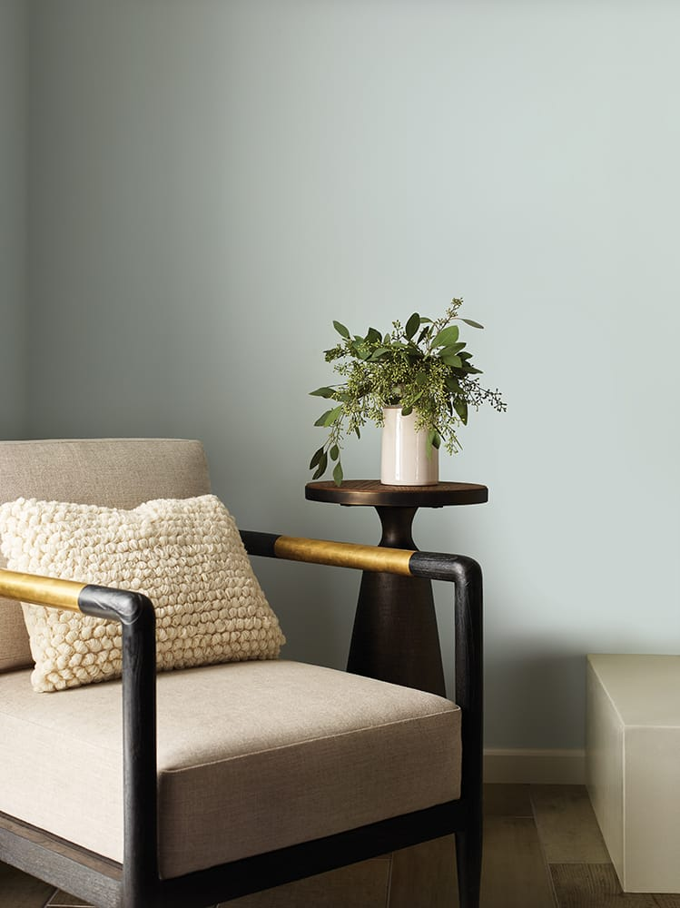 accent chair with textured pillow and side table against soft gray wall